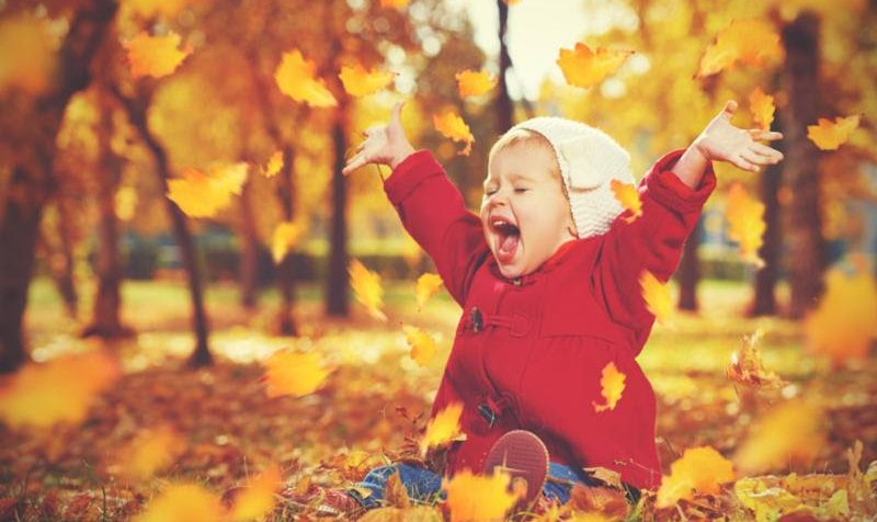 Baby playing in fall leaves